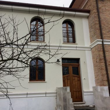 Portone nuovo in legno massello castagno e finestre ad arco in castagno restaurate